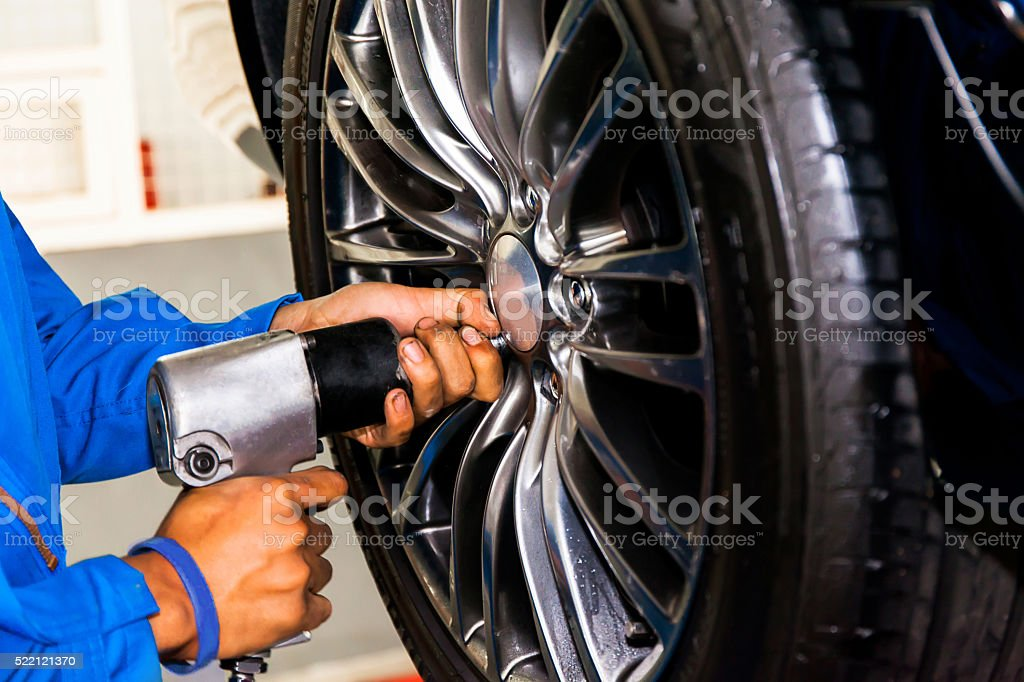 mechanic screwing or unscrewing car wheel at car service garage stock photo