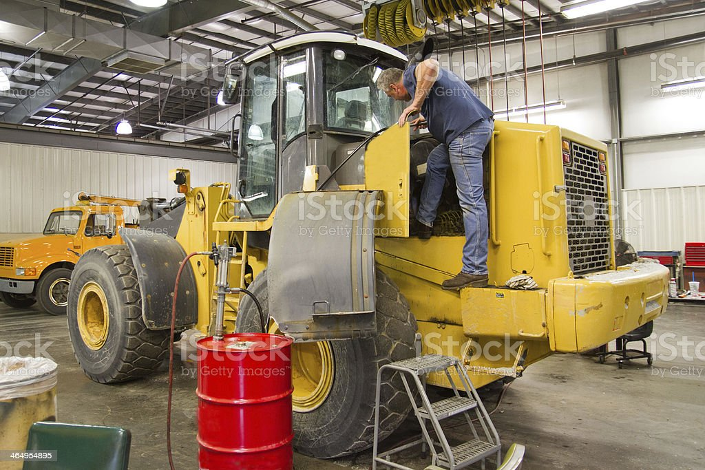 Mechanic servicing front end loader, heavy equipment stock photo