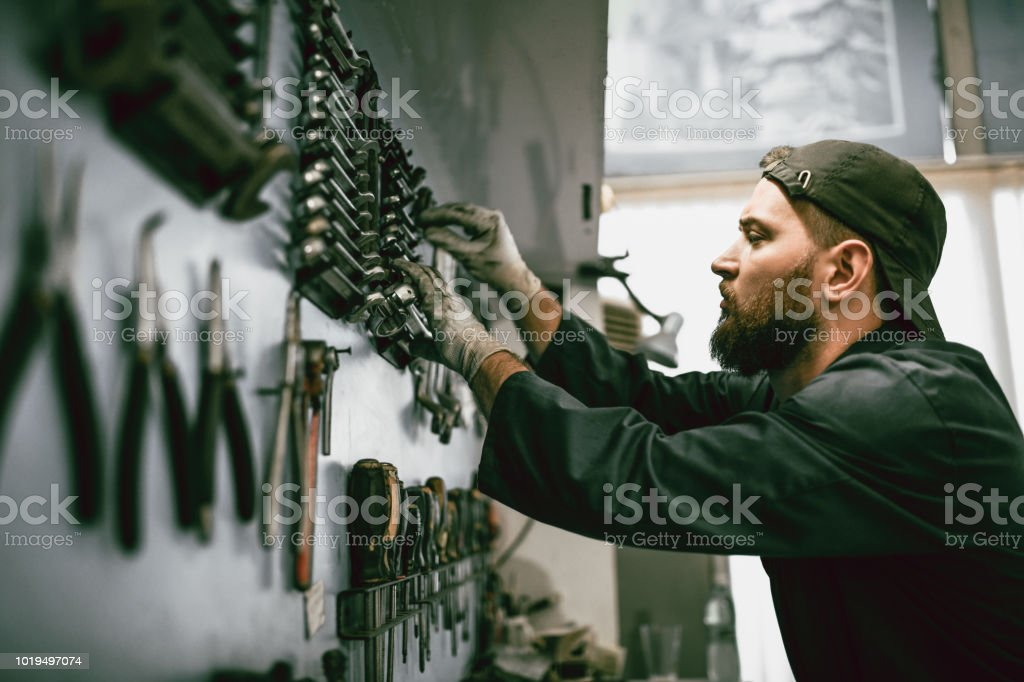 Mechanic Setting Up Cleaned Tools On Wall stock photo