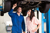 istock A mechanic showing a woman the underside of her car 467715268