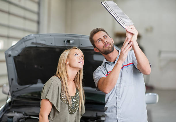 Mechanic shows air filter to female customer during maintenance stock photo