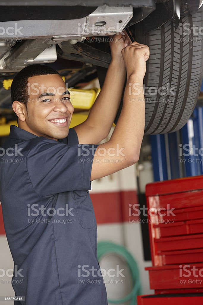 Mechanic smiling while working on car royalty-free stock photo