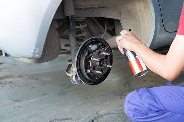 mechanic spray chemical to clean brake – Foto