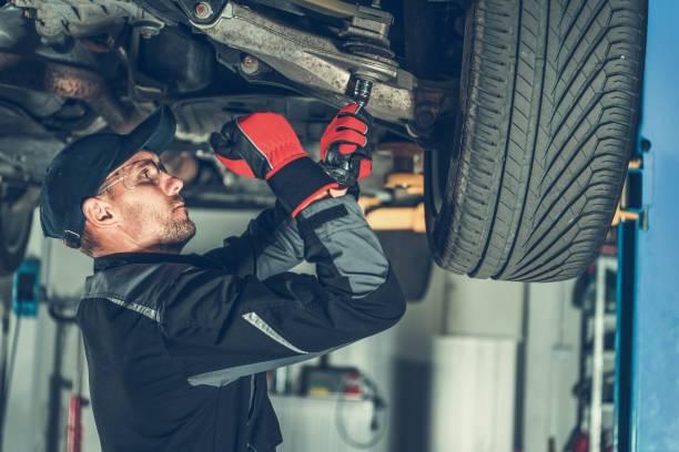 Mechanic Suspension Fix Caucasian Car Mechanic Adjusting Tension in Vehicle Suspension Element. Professional Automotive Service. auto mechanic stock pictures, royalty-free photos & images