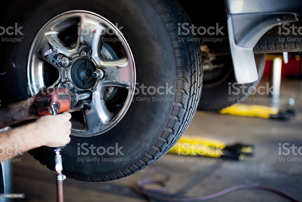 Mechanic Taking Tire off with Power Tool stock photo