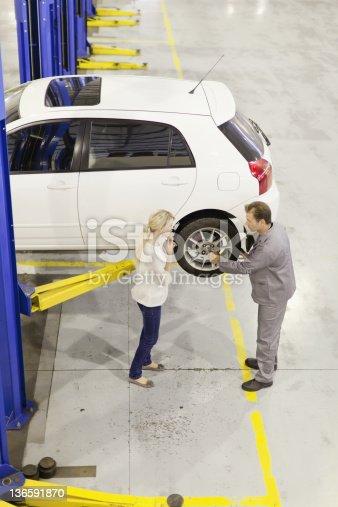 136591855 istock photo Mechanic talking to customer in garage 136591870