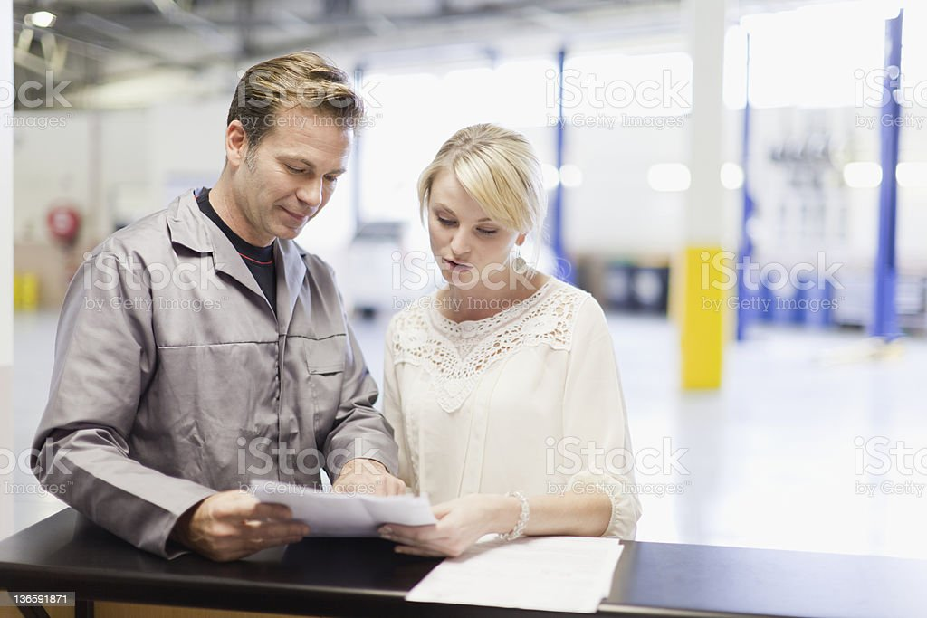 Mechanic talking to customer in garage stock photo