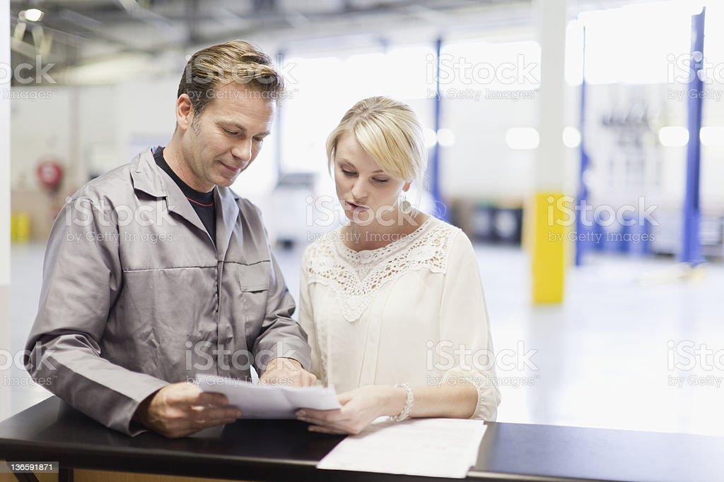 Mechaniker im Gespräch mit Kunden in der garage – Foto