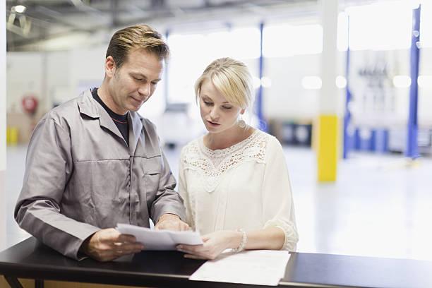 mécanicien parler au client dans le garage - garagiste photos et images de collection