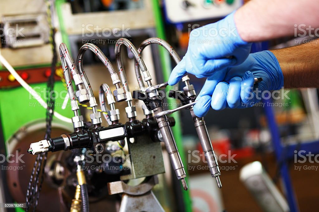 Mechanic testing diesel injector royalty-free stock photo