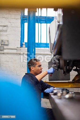 599909112 istock photo Mechanic tightens bolts on brakes 599907666