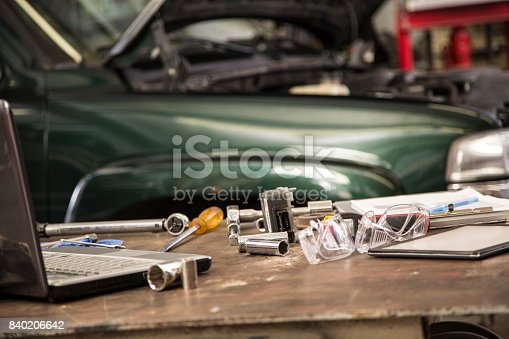 Auto mechanic's tools, laptop, digital tablet on workbench in automobile repair shop.  A truck or SUV is seen in background.  No people in this blue collar image.