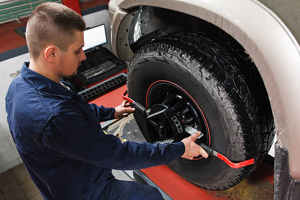 Mechanic tuning aligner for wheel alignment Mechanic tuning aligner for wheel alignment in garage closeup. Professional car maintenance in modern workshop wheel stock pictures, royalty-free photos & images