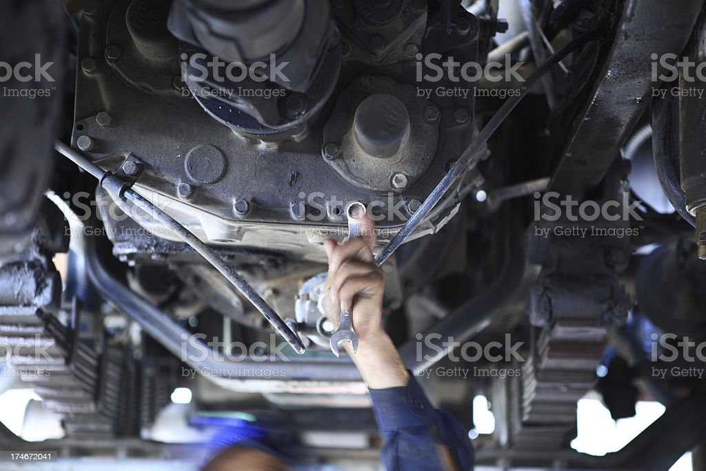 Mechanic under a truck stock photo