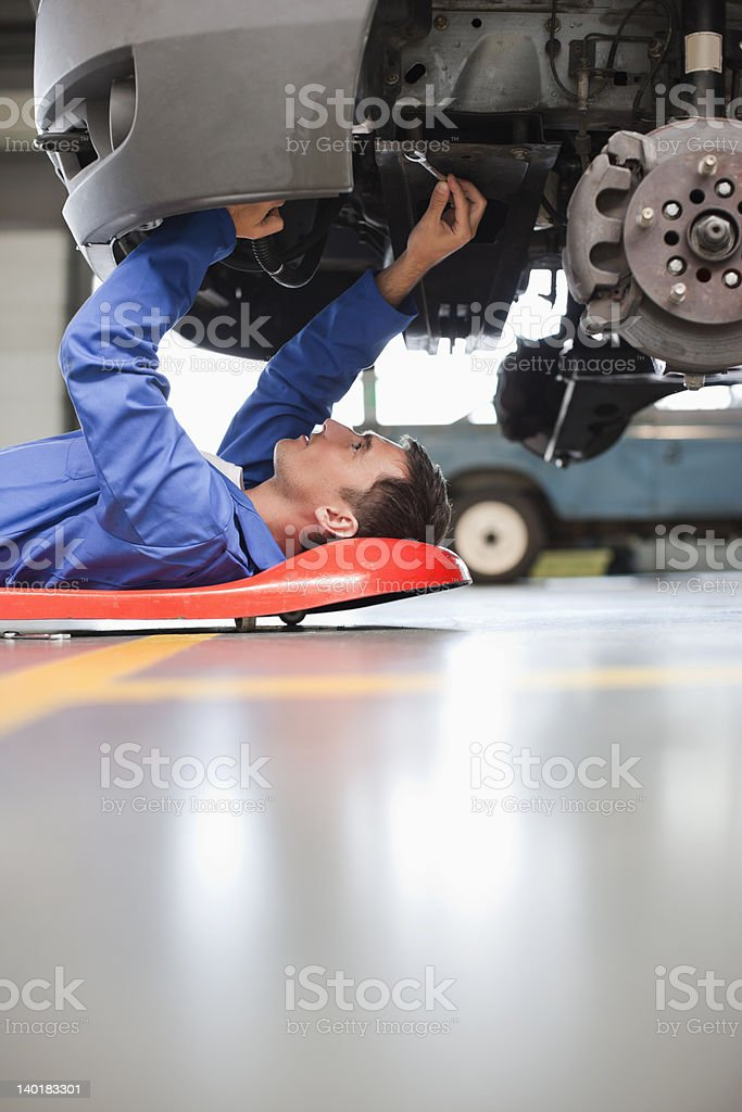 Mechanic underneath car stock photo
