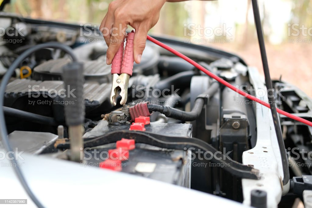 Mechanic Use Jumper Cables To Charge Dead Car Battery Stock