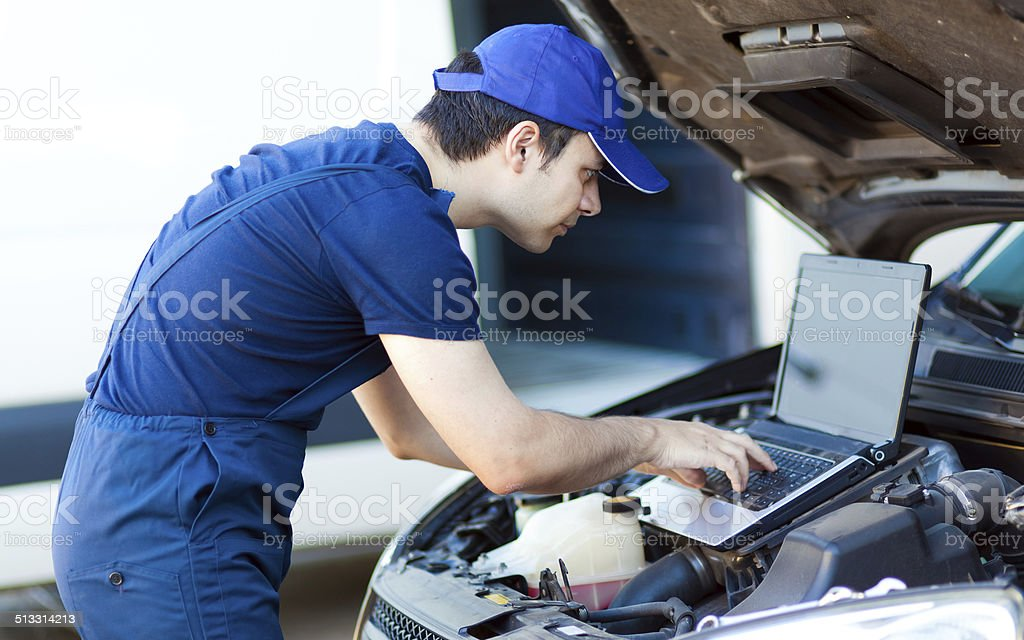 Mechanic using a laptop computer to check the car engine stock photo