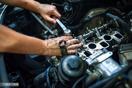 Car mechanic man at the garage fixing the engine. Hands of car mechanic with wrench in garage. Close up hands of unrecognizable mechanic doing car service and maintenance. Auto Service Business Concept. Pro Car Mechanic Taking Care of Vehicle. Checking Under the Car Hood.