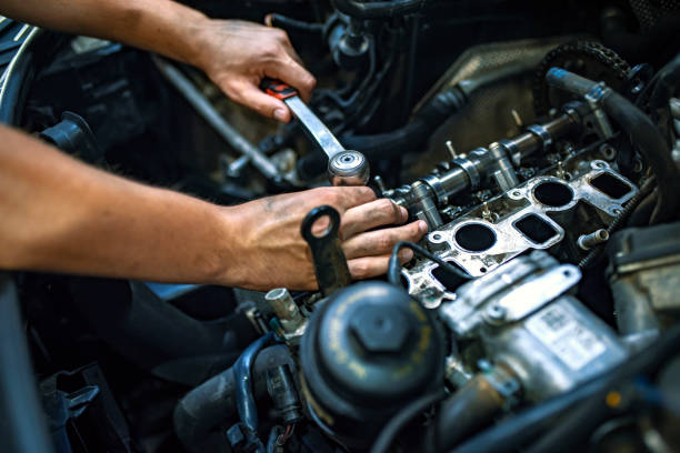 mechaniker mit einem ratschenschlüssel - autowerkstatt stock-fotos und bilder