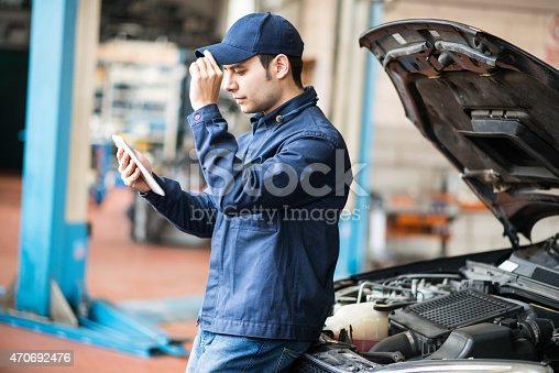 istock Mechanic using a tablet in his garage 470692476