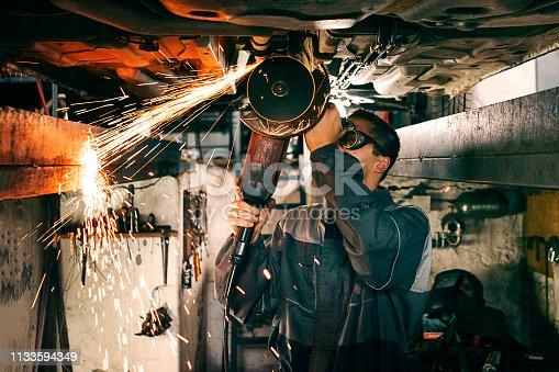 Mechanic using grinding wheel on car bottom making sparks