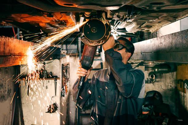 Mechanik mit Schleifscheibe auf dem Fahrzeugboden – Foto