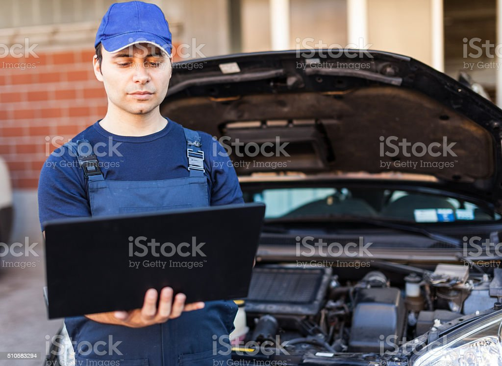 Mechanic using laptop computer to check a car engine stock photo