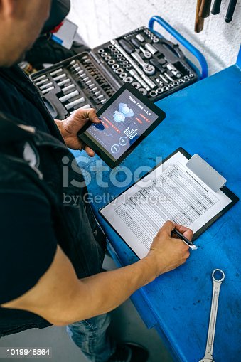 istock Mechanic using tablet app and taking notes 1019948864