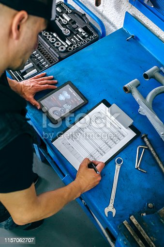 istock Mechanic using tablet app and taking notes 1157062707