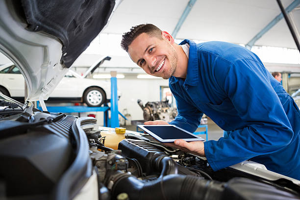 Mechanic using tablet on car Mechanic using tablet on car at the repair garage mechanic stock pictures, royalty-free photos & images
