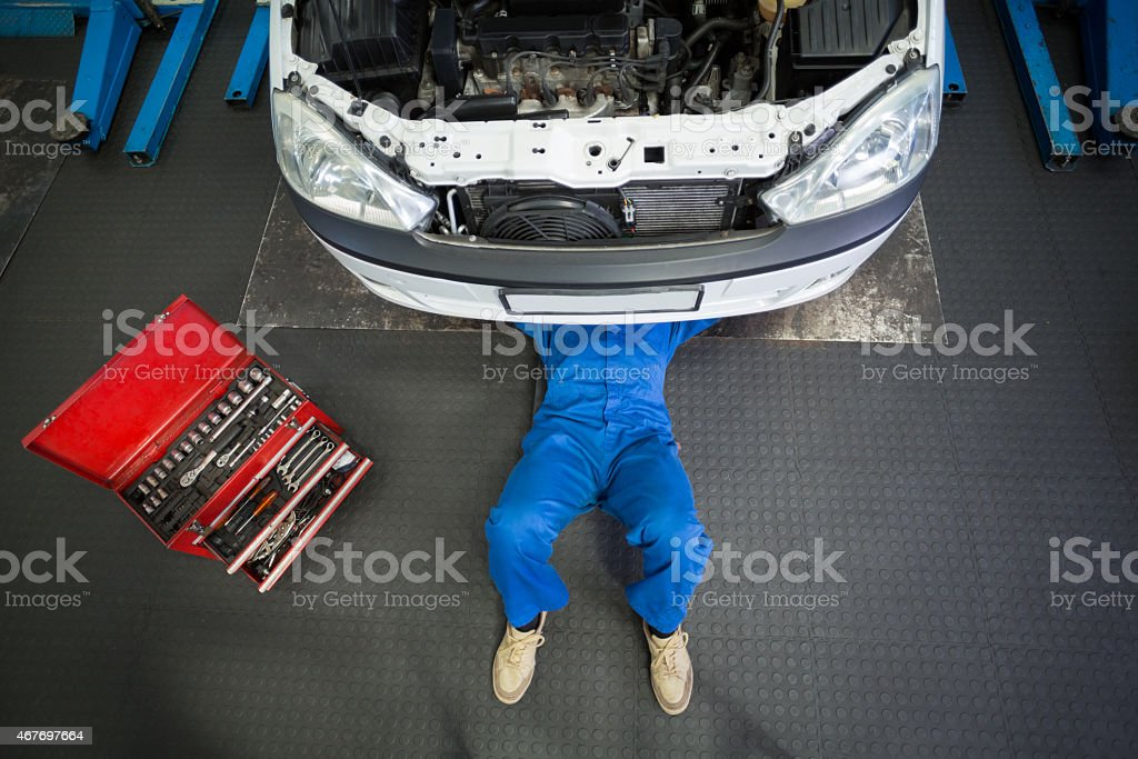 Mechanic wearing blue lying and working under white car stock photo