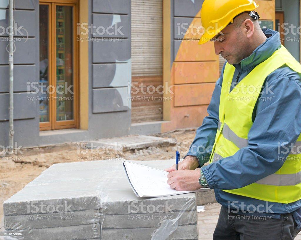 Mechanic wearing protective clothing examining construction site photo libre de droits