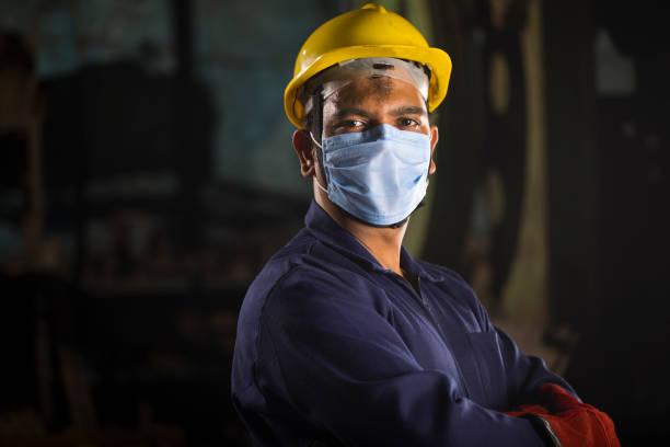 Mechanic wearing protective face mask looking at camera stock photo