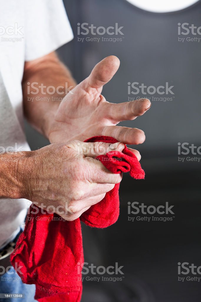 Mechanic wiping hands with towel royalty-free stock photo