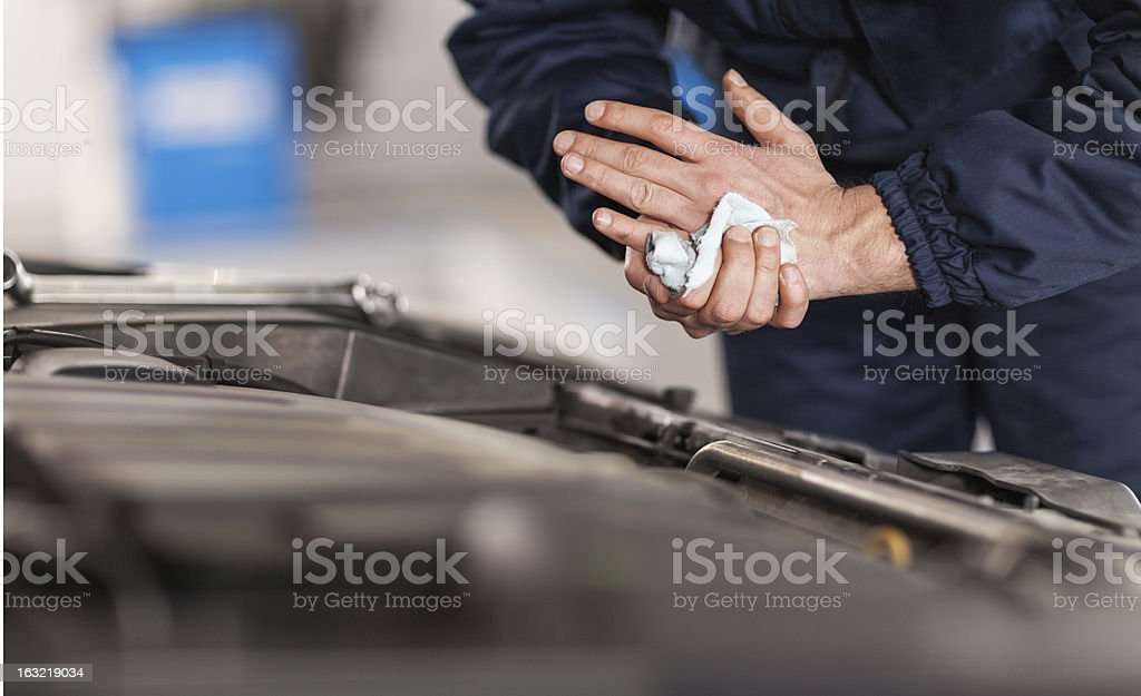 Mechanic wiping his hands clean stock photo