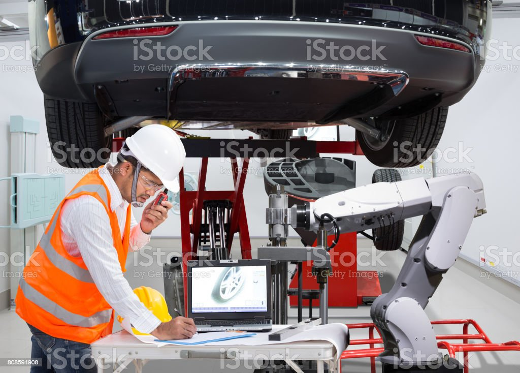 Mechanic with assistance robotic inspection wheel balancing of modern car in automotive industry 4.0 concept stock photo