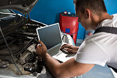 istock Mechanic with diagnostic tool in car workshop 578293902