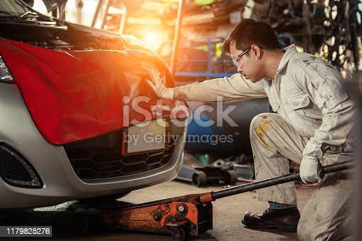 Mechanic with Floor Jack Car Lift. Vehicle Maintenance in the Auto Service Center.