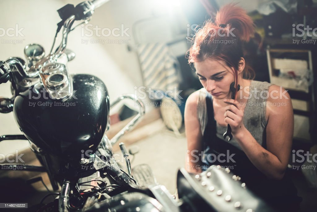 Beautiful mechanic woman attempt to repair motorcycle in a motorcycle...