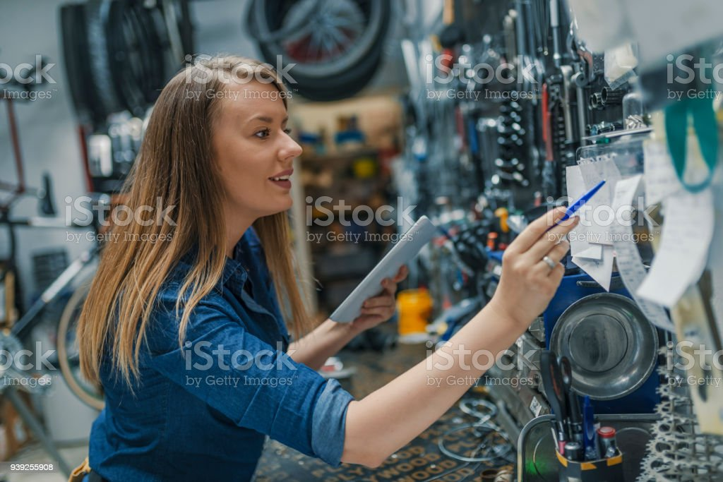 Verify the checklist. Mechanic woman checking something on a...