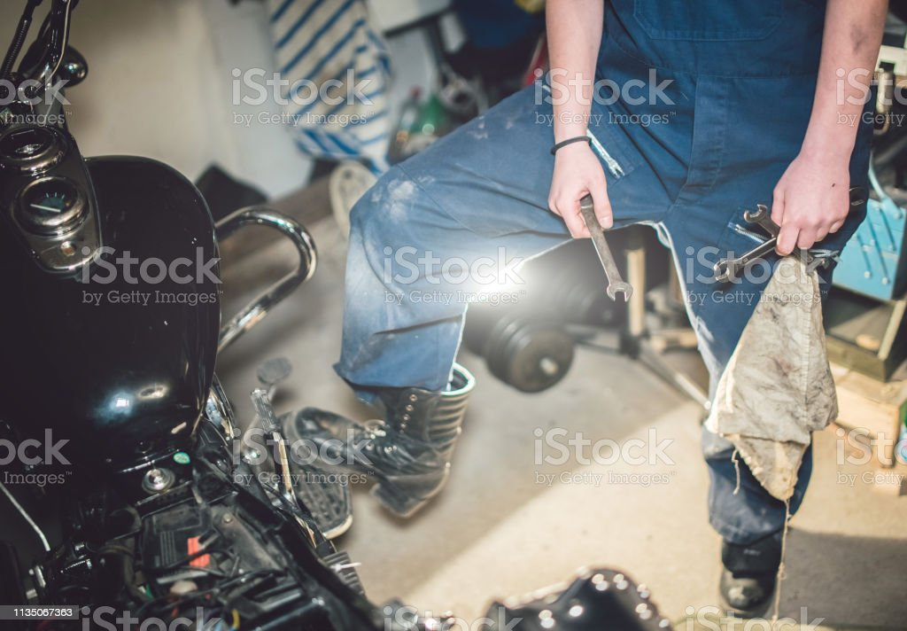 Mechanic woman hold wrench keys in hand and have dirty rag in pocket.