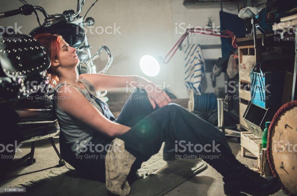 Mechanic woman resting after repair motorcycle in garage.