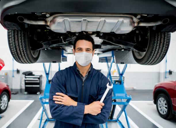 mechaniker arbeitet in einer autowerkstatt mit einer gesichtsmaske, um die ausbreitung des coronavirus zu vermeiden - autowerkstatt stock-fotos und bilder
