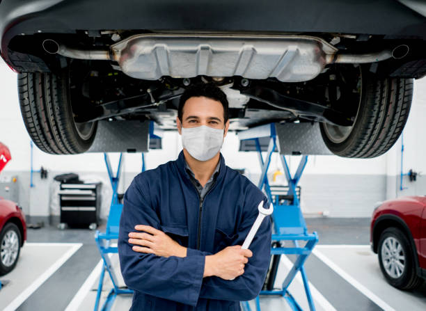mechanic working at a car garage wearing a facemask to avoid the spread of coronavirus - mechanic foto e immagini stock
