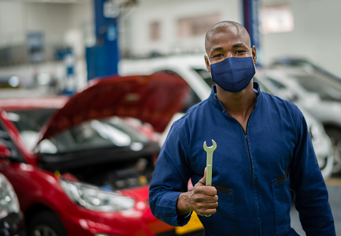 Mechanic working at a garage and wearing a facemask during the COVID-19 pandemic - reopening of businesses