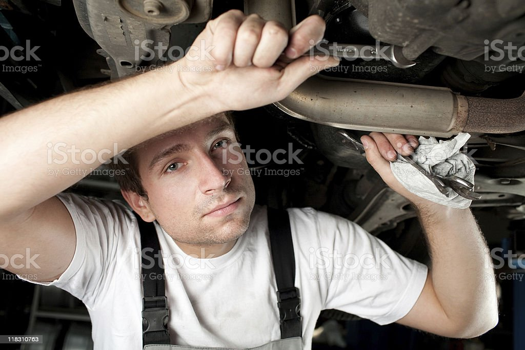Mechanic working below car with wrench royalty-free stock photo