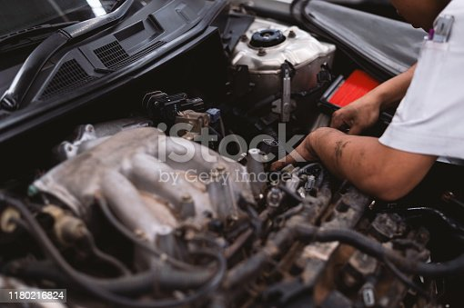 istock mechanic working car maintenance with soft-focus and over light in the background 1180216824