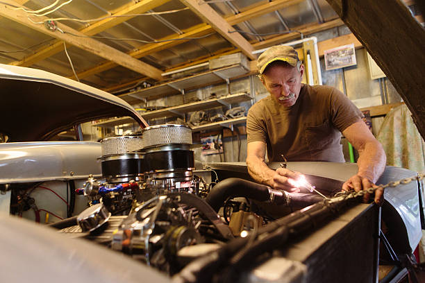 mechanic working in garage shop - classic cars stock photos and pictures