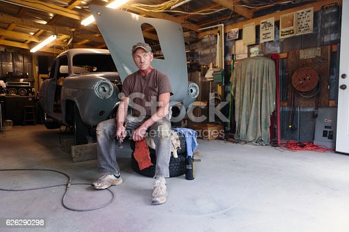 mechanic working in garage shop on antique car