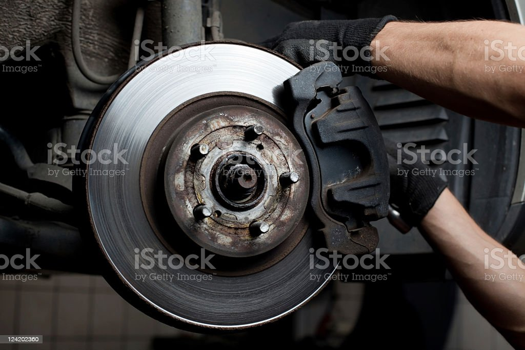 A mechanic working on a brake pad  stock photo